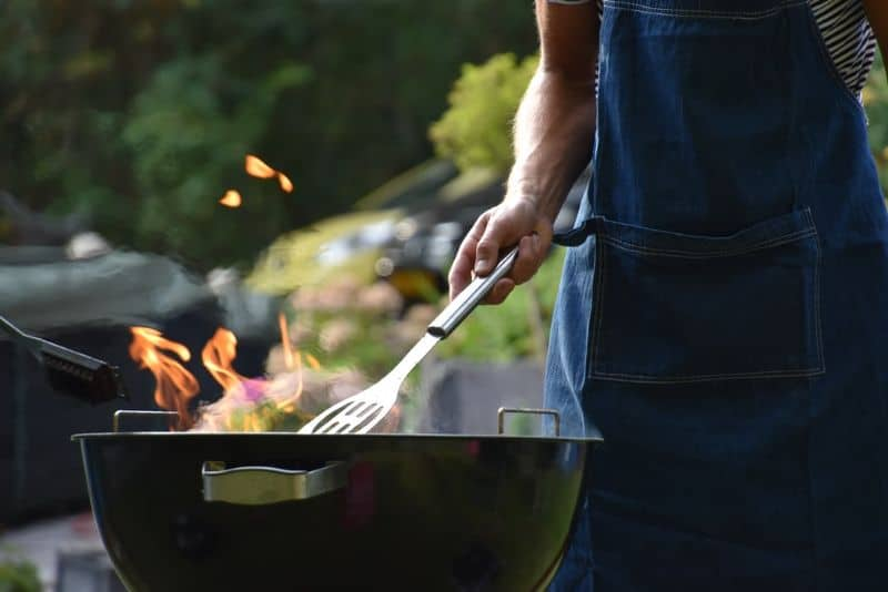 aproned person holding a spatula to an open top kettle grill