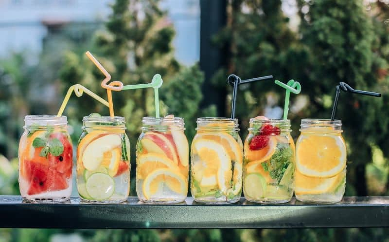 drinks with fruit wedges and swirly straws in mason jars