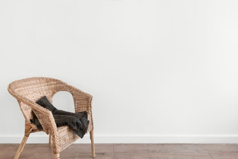 rattan chair with clothing draped on its seat against a large white wall