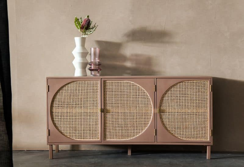 rattan and wood cabinet with flower vase shadowed against brown wall